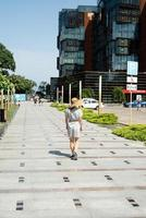 Woman walking by the modern apartment building with green lanes photo