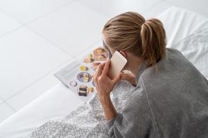 Woman with face mask relaxing lying on the bed reading a magazine photo