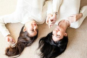 Two best friends laying on the rug at home talking photo