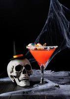 Scary colorful Halloween cocktail with party decorations on dark photo