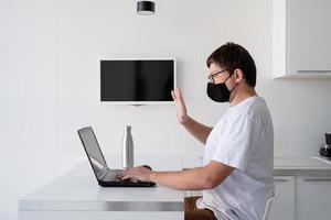 Joven en máscara protectora negra trabajando con un portátil desde casa foto
