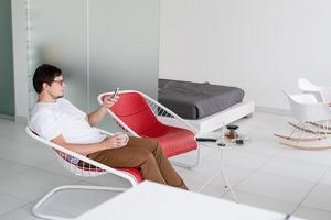 Hombre sentado en una silla viendo la televisión sosteniendo una taza de té y un teléfono foto