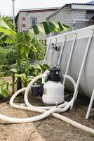 Sand filter plant at a pool in the garden photo