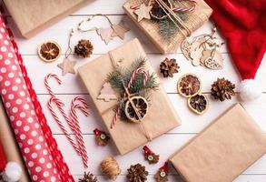 Gift boxes wrappaed in craft paper decorated with pine cones photo