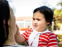 Niña asiática en manos de la madre al aire libre foto