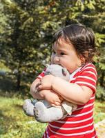 Asian baby girl hugging her toy walking outdoors photo