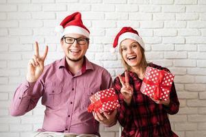 Feliz pareja de Navidad en gorro de Papá Noel sobre fondo de pared de ladrillo blanco foto