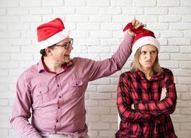 Feliz pareja con gorro de Papá Noel divirtiéndose sobre fondo de pared de ladrillo blanco foto