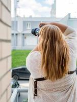Portrait of overweight woman taking pictures with a camera outdoors photo