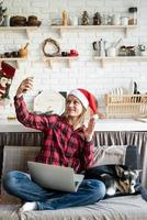 Happy woman in santa hat greeting her friends in video chat on laptop photo