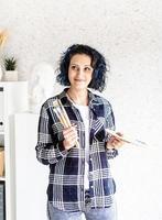 Artista mujer sonriente en su estudio sosteniendo paleta de arte y pintura foto