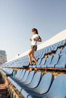 Teenager girl working out at the staduim running down the stairs photo