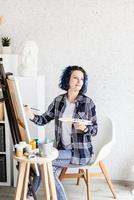Mujer creativa con pintura de cabello teñido de azul en su estudio foto