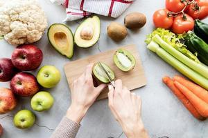 Female hand scutting a kiwi for detox diet top view flat lay photo