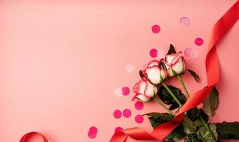 Pink roses with confetti on solid pink background photo