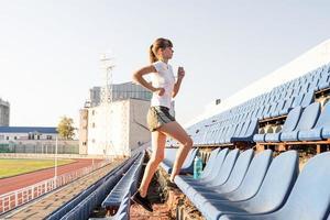 Chica adolescente trabajando en el staduim corriendo escaleras arriba foto