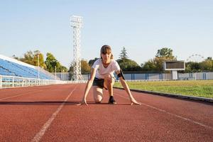 Young woman ready to race at stadium track photo