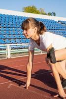 Mujer joven lista para correr en la pista del estadio foto
