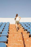 Teenager girl working out at the staduim running up the stairs photo