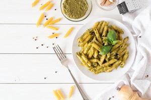 pasta penne vegana en salsa pesto de albahaca vista superior laicos plana foto