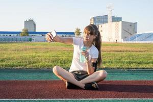 Teen girl making selfie at the stadium after workout drinking water photo