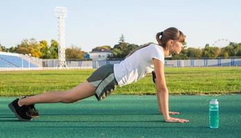 Teenager girl workout standing in a plank position at the stadium photo