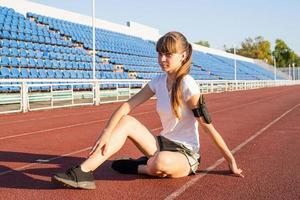 Chica adolescente sentada en la pista del estadio que descansan foto