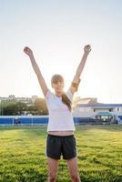 joven deportista de pie en la pista levantando los brazos foto