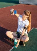 Teen girl making selfie at the stadium after workout photo