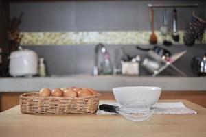 granja de huevos frescos en canasta de madera, tazón de fuente blanco en la cocina de la casa. foto
