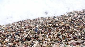 Sea waves are splashing to the pebbles in slow motion video