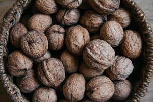 Walnuts in a round wicker basket on a wooden background. Close up. photo