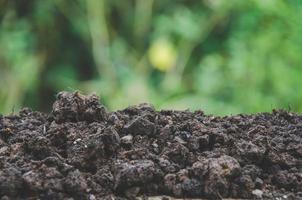 preparación de suelo para la agricultura y montón de suelo con fondo verde. foto