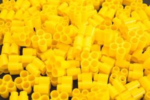 Plastic bricks of yellow color as a background texture photo