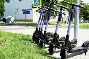 Anapa, Russia 2021- URent electric scooters in a row on a parking photo