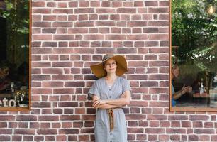 Retrato de una joven y bella mujer sobre un fondo de ladrillos rojos foto