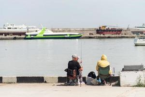 Yalta 2021- People fishing on the embankment, boats and yachts on the background photo