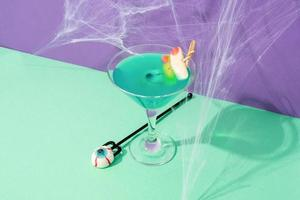 Colorful Halloween cocktails with party on purple and green background photo