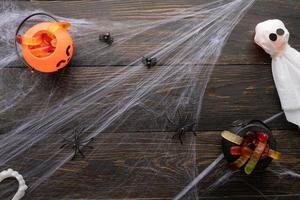 Holiday background with spider web and scary decorations on black background photo