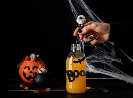 Scary colorful Halloween cocktail with party decorations on dark background photo