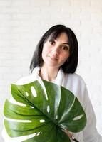 Middle eastern woman wearing bath towels holding a green monstera leaf photo