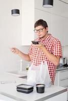 Hombre sujetando una bolsa de plástico desechable con entrega de comida en la cocina foto