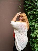Overweight woman posing on the brown solid wall on the street photo