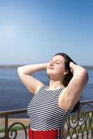 Beautiful young woman enjoying the sun standing by the river photo