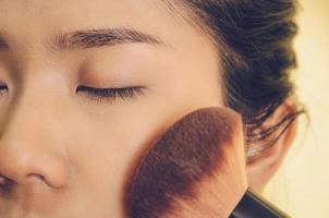 rostro de belleza de mujer asiática mediante la aplicación de pinceles en la piel con cosméticos. foto