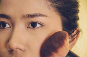 Beauty face of Asian woman by applying brushes on skin by cosmetics. photo