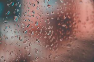 Fondo y papel tapiz por gota de lluvia y gotas de agua en la ventana. foto