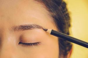 rostro de belleza de mujer asiática aplicando lápiz de cejas sobre la piel. foto