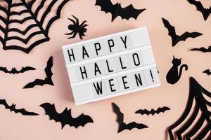 concepto de halloween. murciélagos y arañas sobre fondo rosa. foto