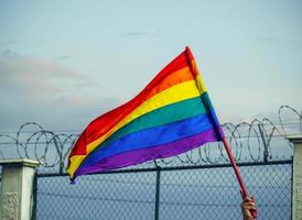 LGBTQ  flag with a barbed wire fence in the background. photo